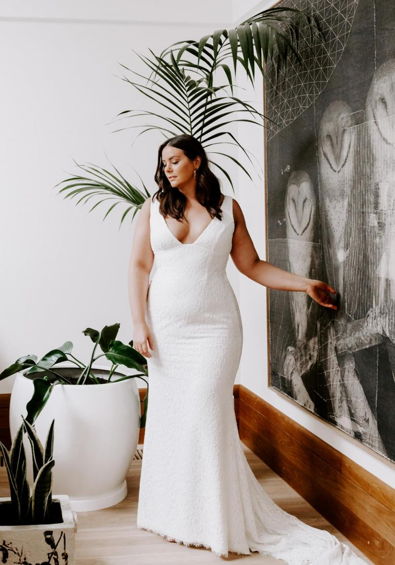 The Adina Curve gown by Karen Willis Holmes, plunging neckline lace plus size wedding dress.
