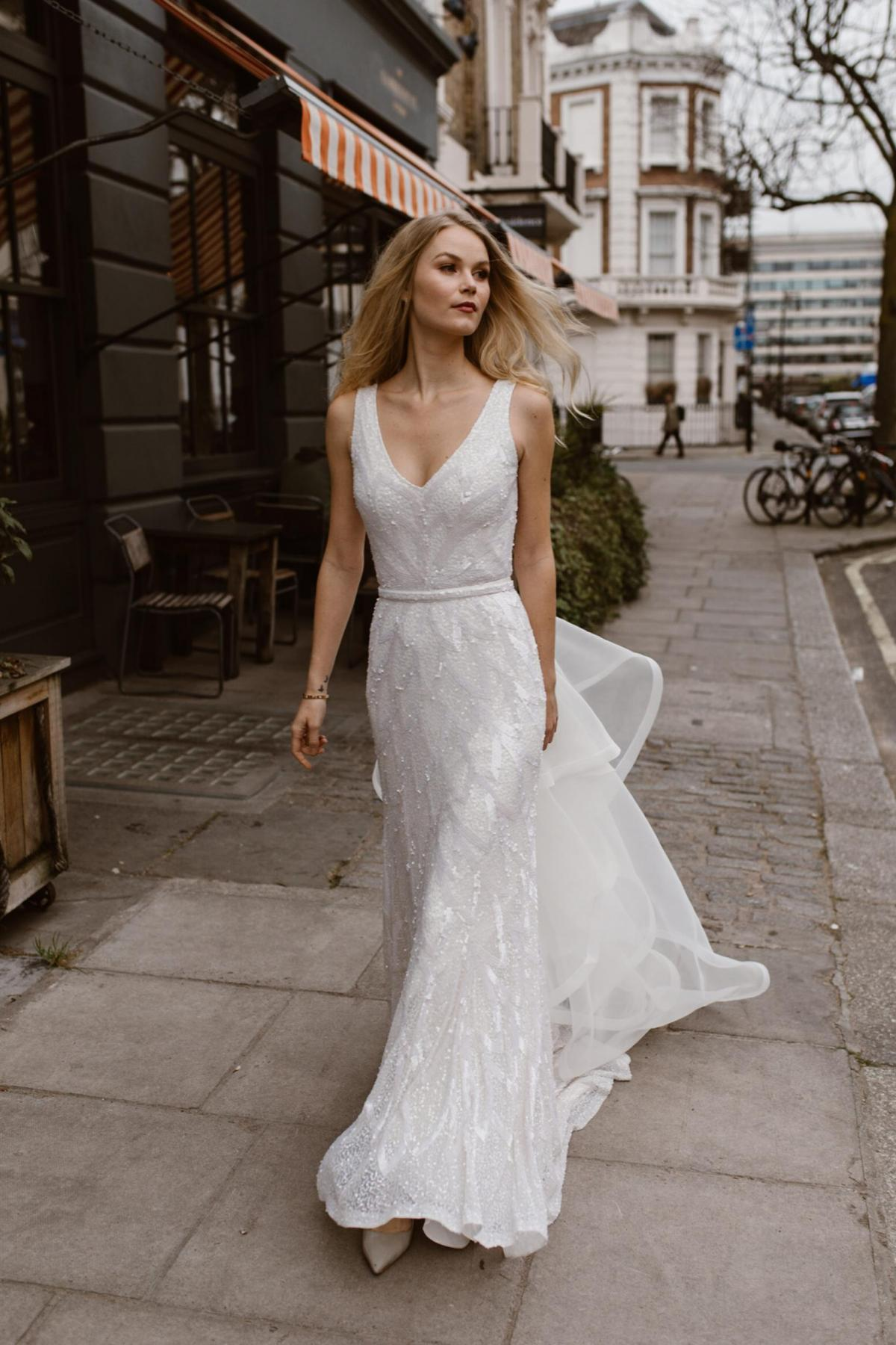 The Rhiannon gown by Karen Willis Holmes, v-neck beaded wedding dress shown with detachable train.