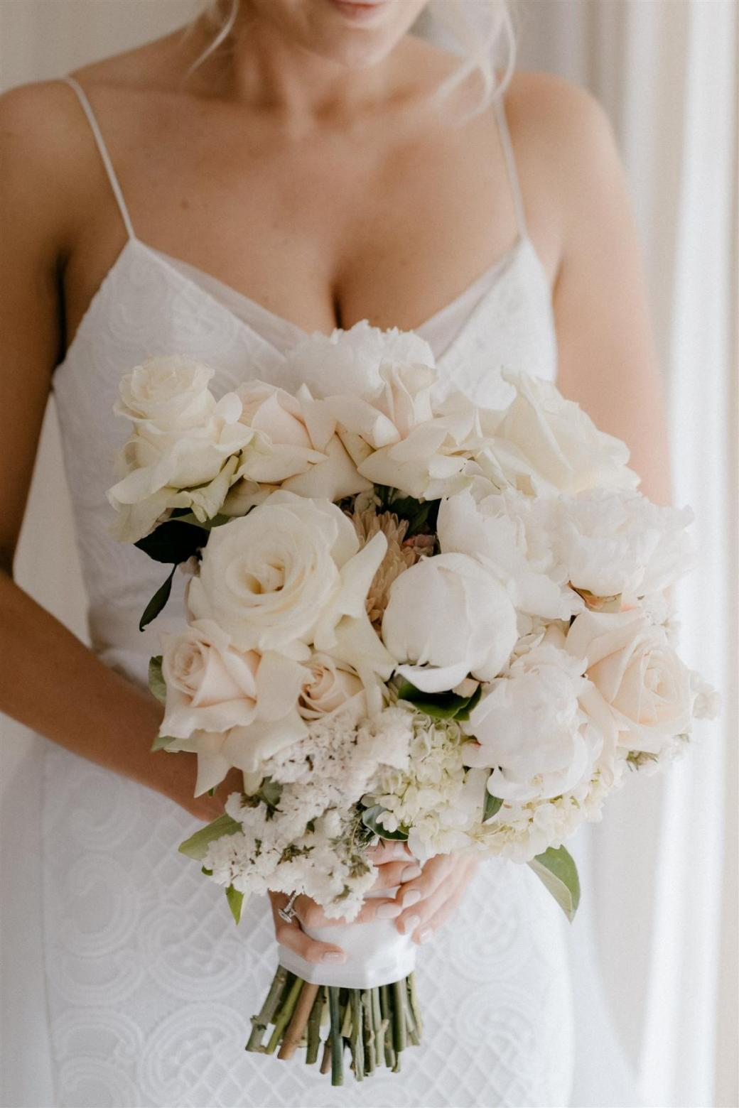 Bride in Elodie lace wedding dress by Karen Willis Holmes holding timeless bridal flowers