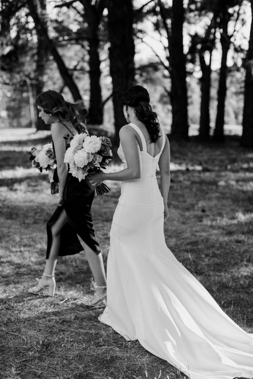 KWH real bride Rachael walking with a timeless bouquet. Rachael wears our minimalistic Violet gown.