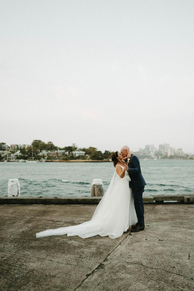 Bride and groom in Sydney Harbour, bride wearing AISHA gown by Karen Willis Holmes; a modern Bespoke wedding dress
