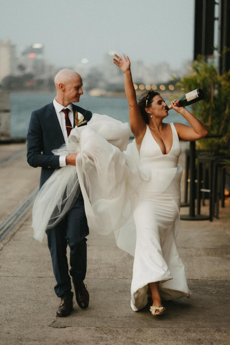 KWH bride and groom celebrating wedding with drinks in Sydney Harbour; Bride wearing AISHA gown by Karen Willis Holmes