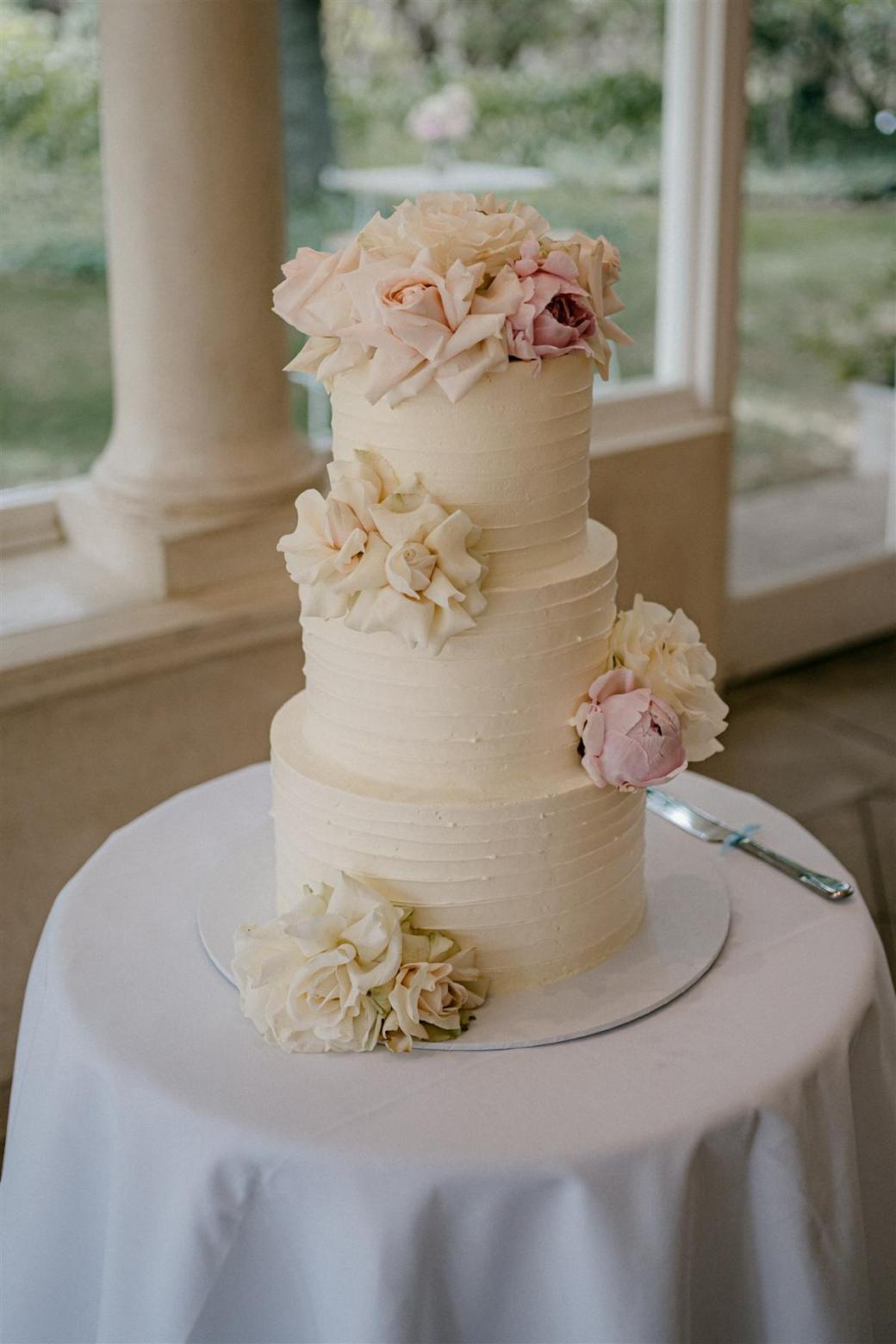KWH bride Ashleigh's cream wedding cake, featuring a rose floral detail.