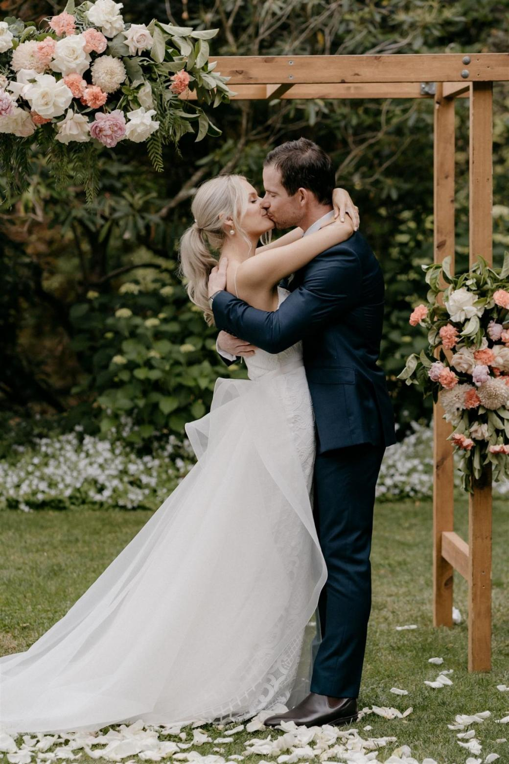 KWH bride Ashleigh and Adrian sharing a kiss at their country wedding; Ashleigh wears the dramatic Oval Trains with her Elodie gown by Karen Willis Holmes for ceremony look.
