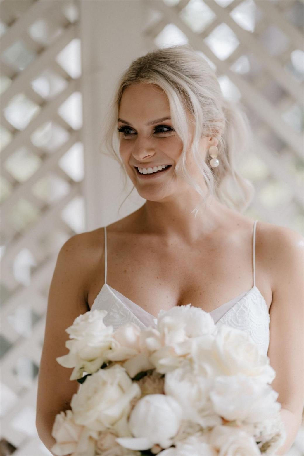 KWH bride Ashleigh smiling at her real wedding; wearing the lace Elodie gown with modesty panels for coverage.