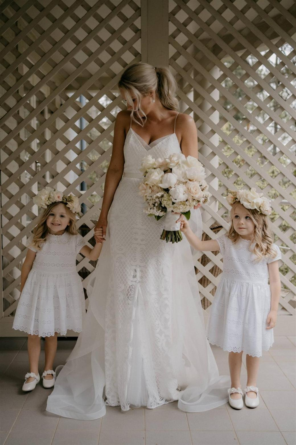KWH bride Ashleigh with her two flower girls, holding her pink and white florals wearing the Elodie gown, a lattice lace wedding dress with spaghetti straps.