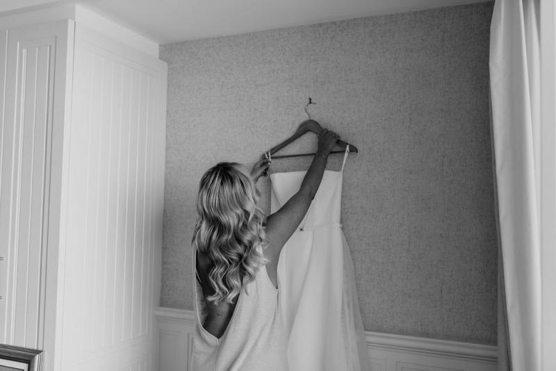 Bride Celeste getting ready in her ESTHER gown; featuring a strapless bodice with a fitted pencil skirt underneath, and a full overskirt.