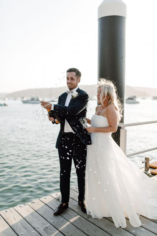 KWH bride Celeste & Daniel celebrating with champagne; wearing the Bespoke ESTHER gown, a modern ball-gown style wedding dress.