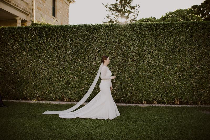KWH bride Cassie looking elegant in her Jemma wedding dress; a bohemian wedding dress with lace sleeves and a v-neck.
