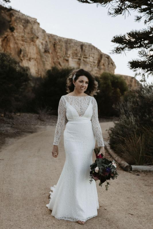 Karen Willis Holmes bride Meagan wearing the Karina gown; featuring a modern U-shaped plunging neckline with an illusion lace boat neck overlay and long fitted lace sleeves.