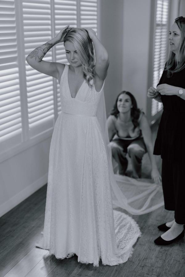 Karen Willis Holmes bride Megan getting ready with bridesmaids for romantic wedding, wearing the Nadia gown; an edgy and romantic lace wedding dress with a V-neck and side split.