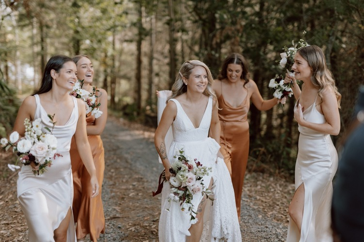 Real bride Megan walking with bridesmaids, holding vibrant bridal bouquet and wearing the Nadia gown; a lace wedding dress for the bohemian bride.