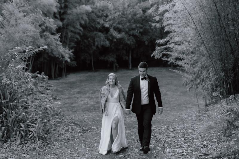 Real bride Megan walking with husband, wearing the Nadia gown; a lace wedding dress for the bohemian bride, featuring a V-neck and side split.