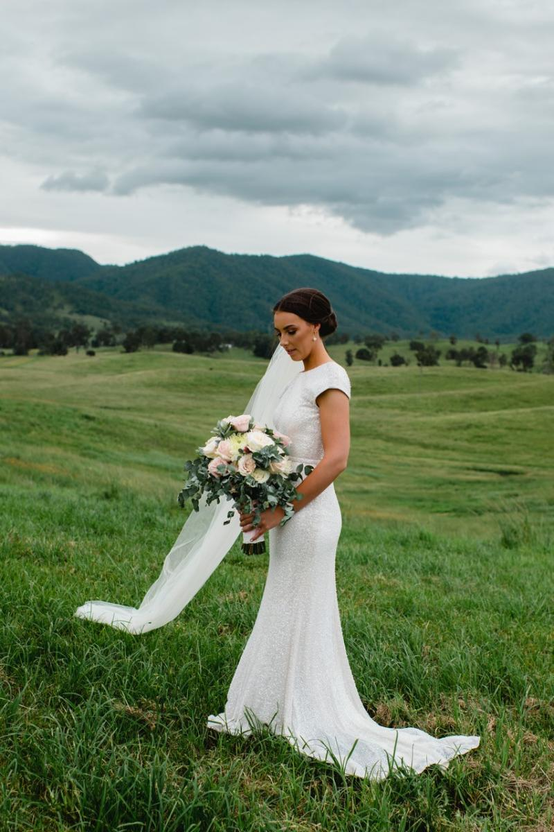 Real bride Elly wears the Annette wedding dress by Karen Willis Holmes; featuring cap sleeves with a high neck and low back.