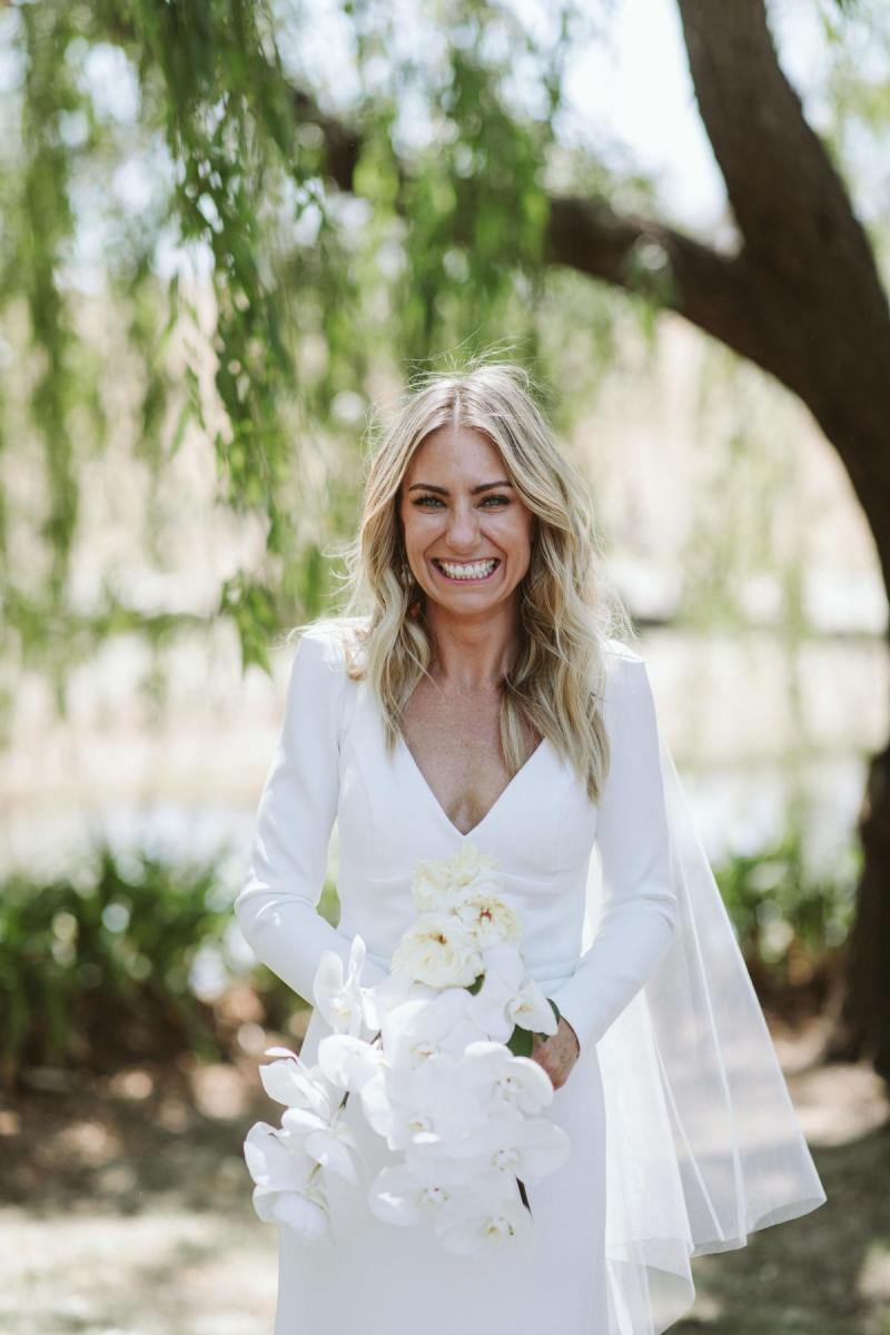Real bride Annabelle wears the long-sleeve Aubrey gown, a timeless wedding dress by Karen Willis Holmes.