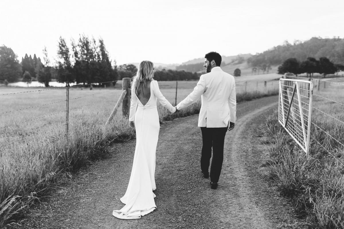 Real bride Annabelle with husband Marc on open country road at farm wedding, bride wearing the timeless Aubrey dress with long sleeves and a deep V back.