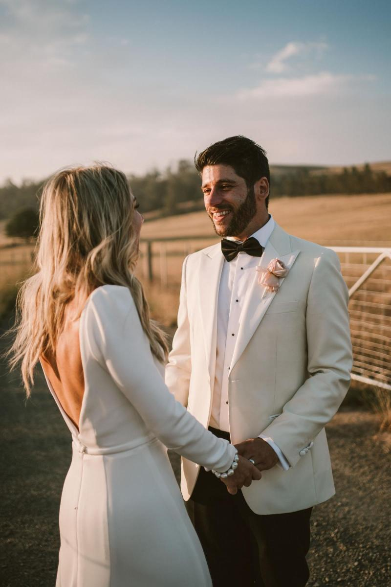 Real bride Annabelle with new husband at sunset on country family farm wedding; bride wears the long-sleeved Aubrey gown by Karen Willis Holmes.