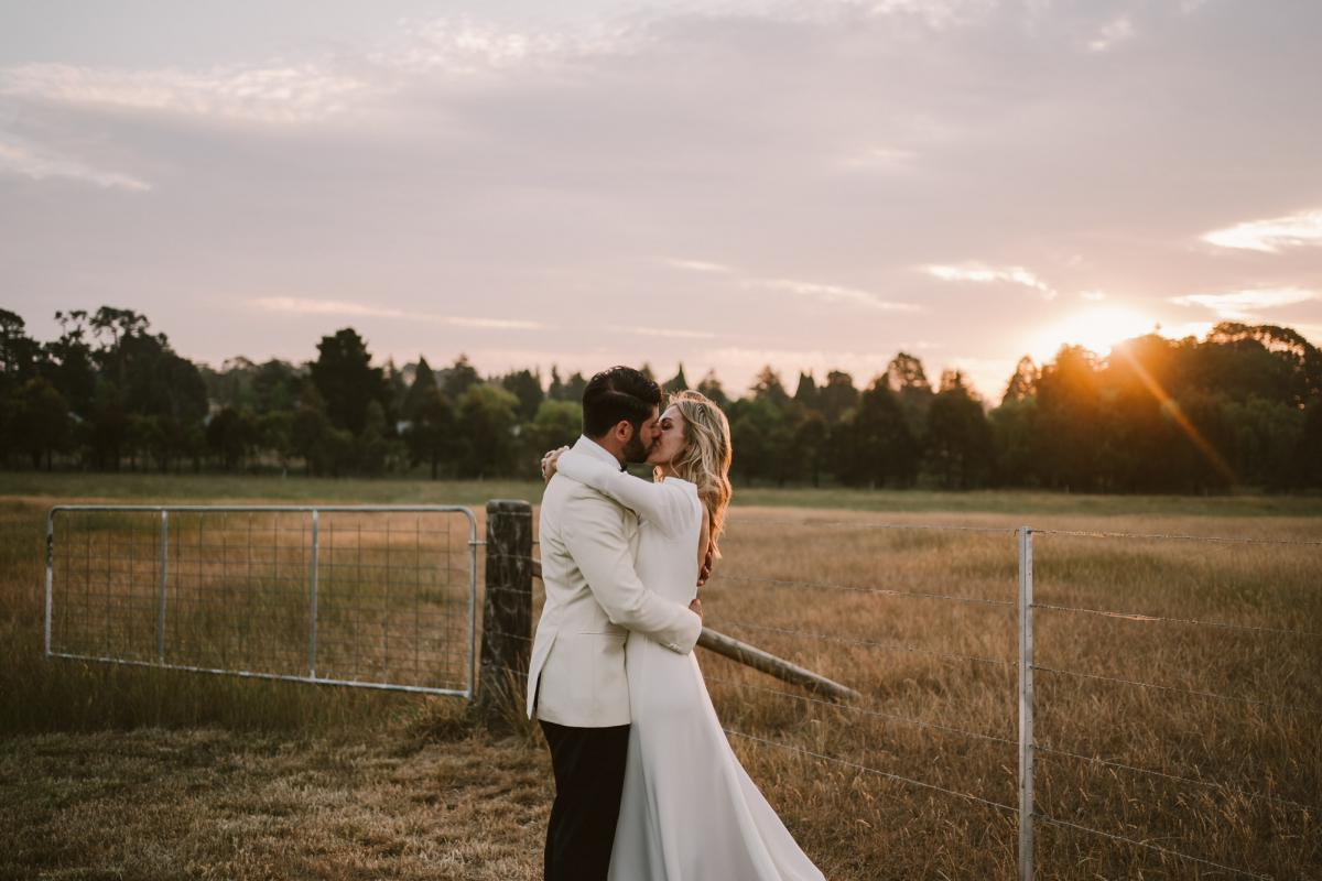 Real bride Annabelle & husband Marc sunset kiss at country farm wedding, bride wearing the long sleeve Aubrey wedding dress by Karen Willis Holmes.