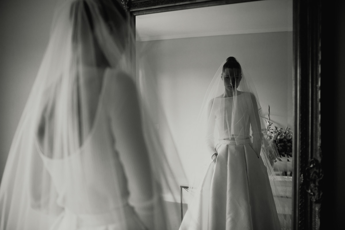 Bride admires herself in Bespoke Melanie wedding skirt by Karen Willis Holmes with veil over the face