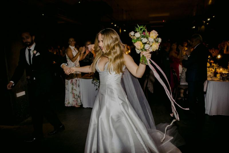 KWH bride Hannah at her festive wedding reception, holding her vibrant rose bridal bouquet and wearing the bespoke Taryn Nina gown, a timeless wedding dress.