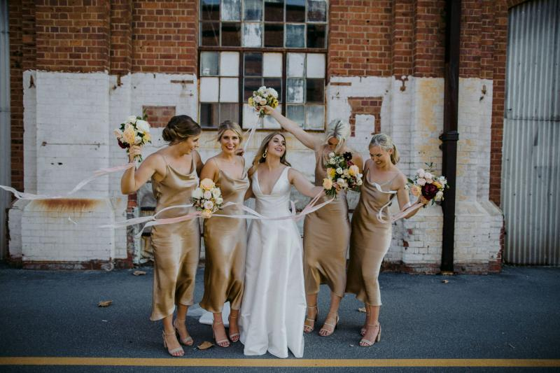KWH bride Hannah with her bridesmaids, holding a vibrant bouquet & wearing the Taryn Nina gown; a Bespoke wedding dress with sexy edge.