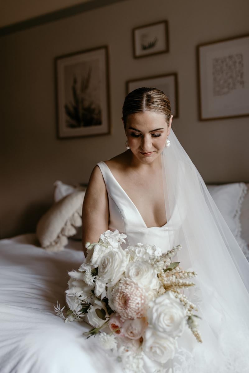 Close up of bride admiring flowers in made to order bespoke wedding dress Taryn Camille by Karen Willis Holmes
