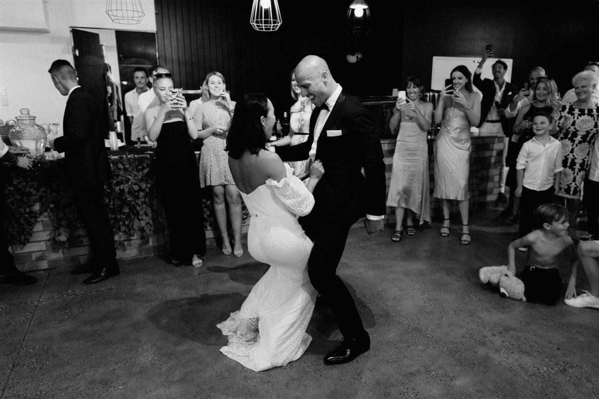 Bride wears Wild Hearts made to order lace off the shoulder Vivienne gown by Karen Willis Holmes dancing with husband at elegant reception