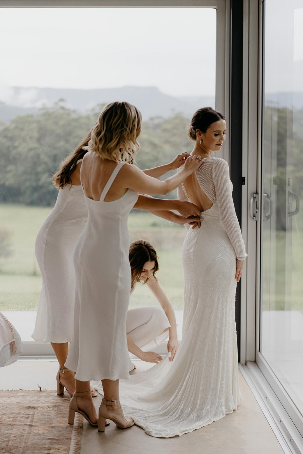 KWH bride Anna being dressed by her bridesmaids; wearing the Cassie gown with a long train.