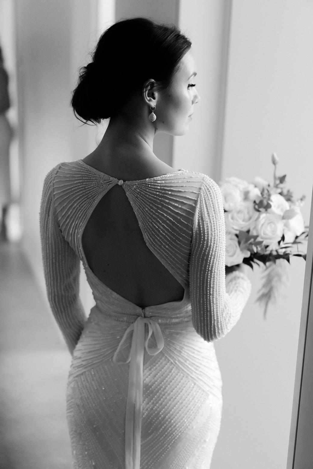 B&W image of Karen Willis Holmes bride Anna wearing the Cassie gown with an open back and holding a timeless bouquet.