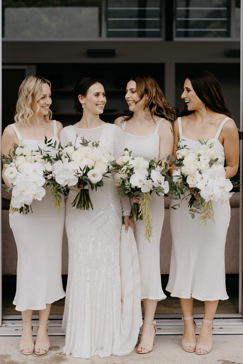 KWH bride Anna with her bridesmaids holding their bouquets. Anna wore the Cassie wedding dress.