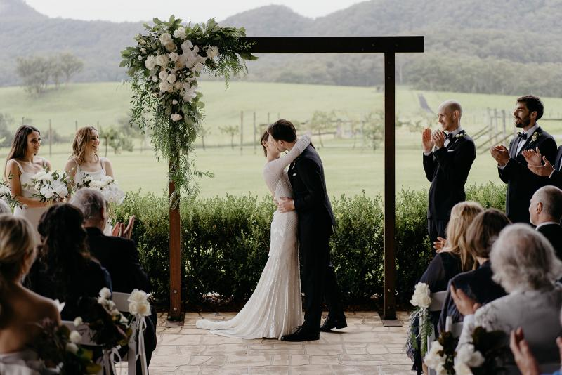 KWH bride Anna kissing her husband Julian under their arbour; wearing the Cassie wedding dress.