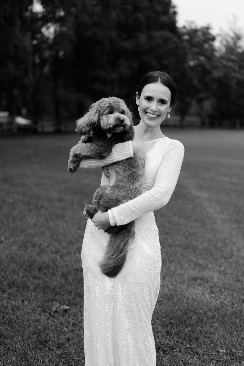 B&W image of Anna with her dog. Wearing the Cassie wedding dress by Karen Willis Holmes.