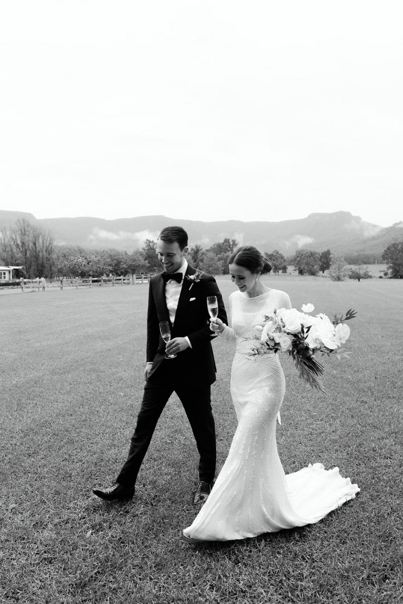 B&W image of Karen Willis Holmes bride Anna walking with husband Julian. Holding her bridal bouquet and glass of champagne. Wearing the Cassie wedding dress.