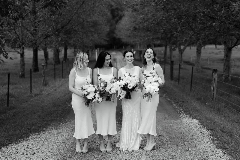 Karen Willis Holmes bride Anna and her bridesmaids; bride wearing the Cassie gown with an open back and long train.