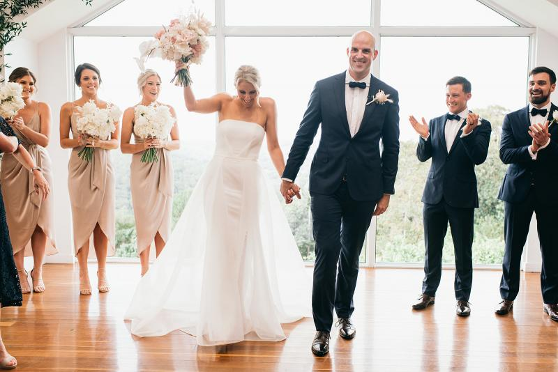 KWH bride Samantha and husband Adam walking down the aisle. Couple is surrounded by their wedding party as bride celebrates with bouquet in the air. Samantha wears the Esther wedding dress with a fitted skirt and long train.