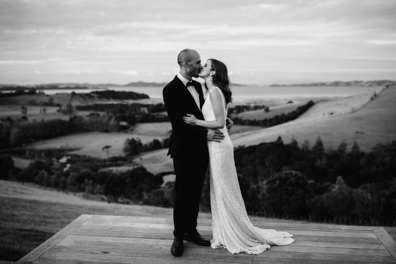 B&W image of KWH bride Tash and husband Josh sharing a kiss; bride wearing the Lola gown with a low back.