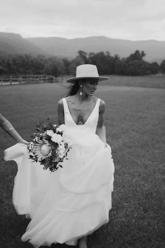 Real bride Sarah wears the Taryn Marina Bespoke wedding dress to her country wedding, posing with a straw fedora and native bouquet for wedding portraits.