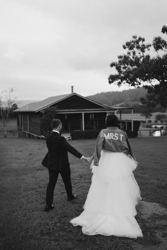 Sarah & Phil hand in hand at real country farm wedding, bride wears the Bespoke Taryn Marina wedding dress by Karen Willis Holmes with a custom denim bridal jacket.