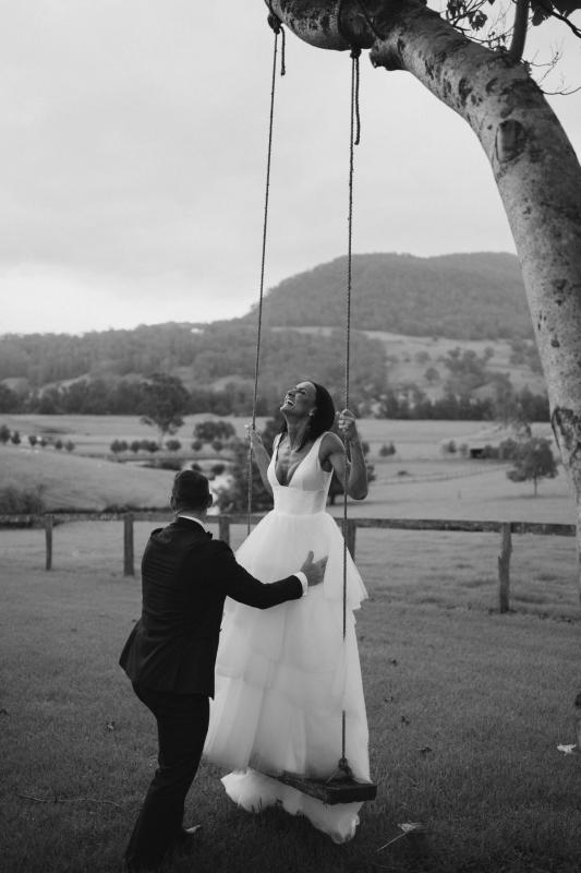 Real couple Sarah & Phil celebrate their country farm wedding, bride wears the Taryn Marina gown by Karen Willis holmes, bride sits on swing for wedding portraits.