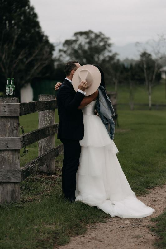 KWH couple sharing a kiss at their country wedding, real bride wearing the Taryn bodice and Marina skirt, a Bespoke wedding dress by Karen Willis Holmes.