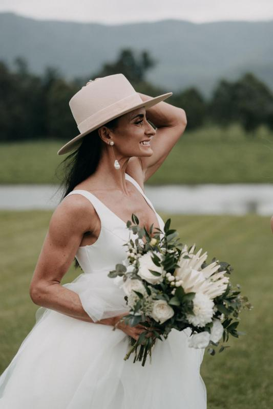 Real bride Sarah wears the Taryn Marina Bespoke wedding dress to her country wedding, posing with a straw fedora for wedding portraits.