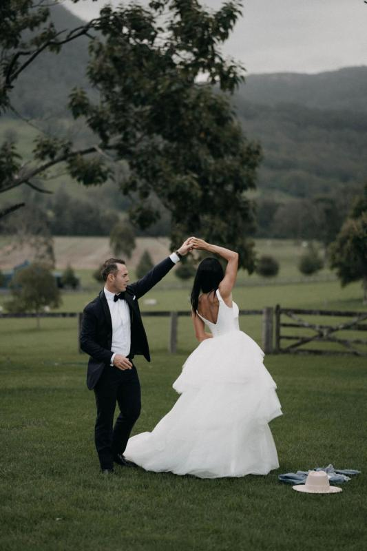 Real couple Sarah & Phil dancing at their country farm wedding, bride wears the Taryn Marina gown by Karen Willis holmes.