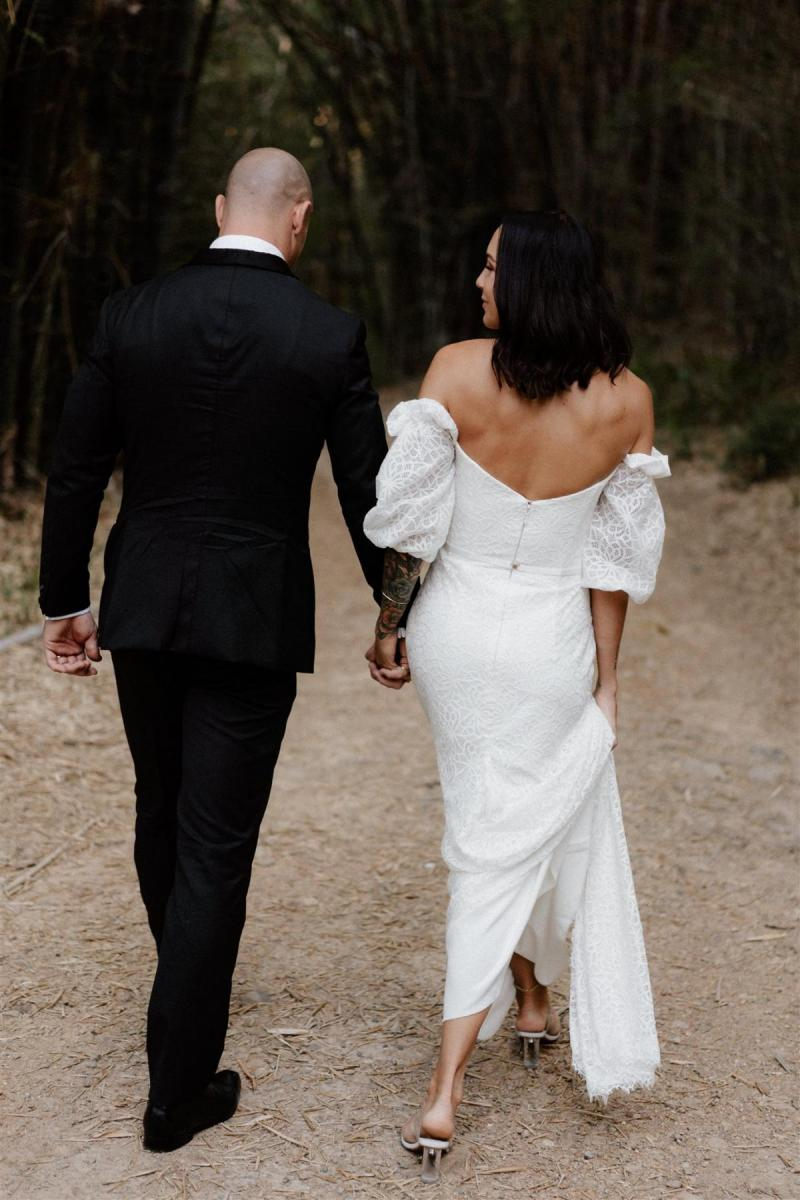 Real bride Lidia wears the Vivienne wedding dress, a lace wedding dress with balloon sleeves and dramatic train by Karen Willis Holmes for the boho bride