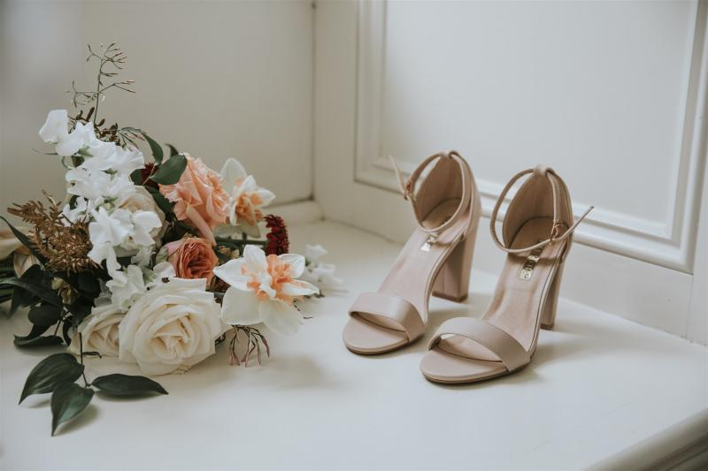 Real bride Lucy's wedding accessories, featuring colourful blooms and nude heels.