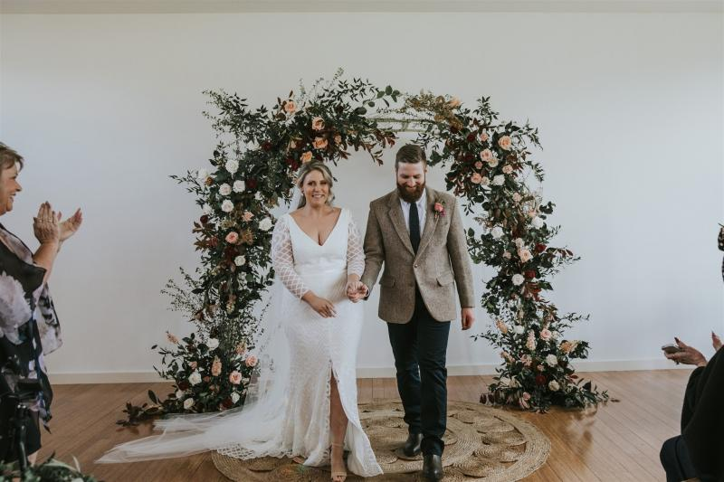 Curvy bride Lucy standing under flower arch at wedding ceremony, bride wearing the Bobby gown; a modern lace wedding dress with long sleeves by Karen Willis Holmes.