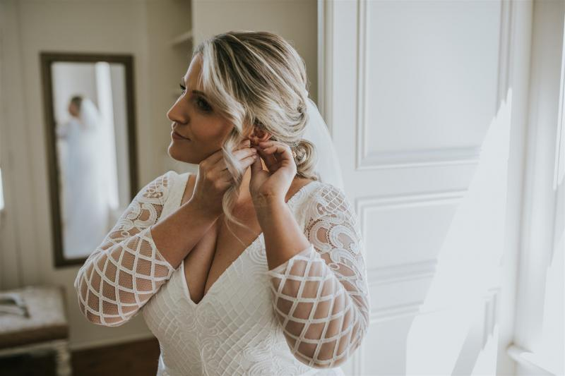 Curvy bride Lucy getting ready on her wedding day, wearing the Bobby gown with custom sleeves; a modern lace wedding dress by Karen Willis Holmes.