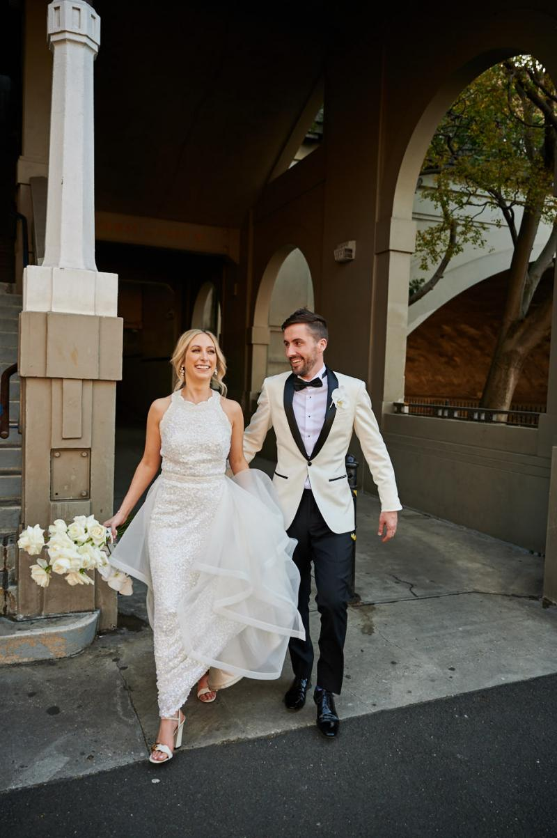 Real bride Claire wears the Cindy gown, a beaded halterneck wedding dress by Karen Willis Holmes. New husband holds her train while walking out of the venue.
