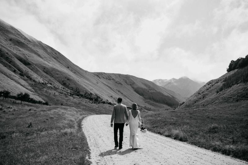 KWH real bride Lauren and Will walk together a in front of magical New Zealand landscape. The bride wears the modern sleeved Nikki gown