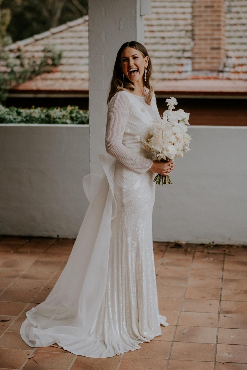 Real bride Penelope wears the Cassie gown; a long sleeve art deco beaded wedding dress from the Luxe collection by Karen Willis Holmes, along with the Oval detachable trains.