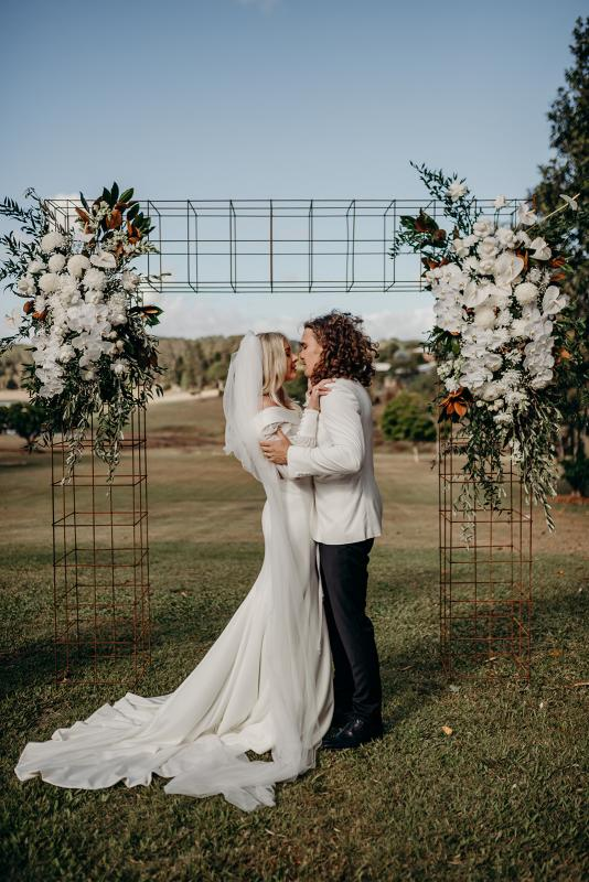 Real bride Hannah kisses husband Rich at wedding ceremony under floral arbour, wearing the Lauren gown with customised long sleeves from the Nikki gown by Karen Willis Holmes